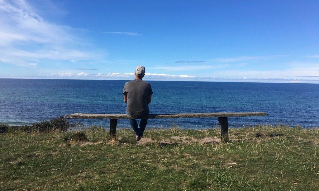 Mann auf einer Bank in Gilleleje sitzend mit Blick auf die Ostsee.