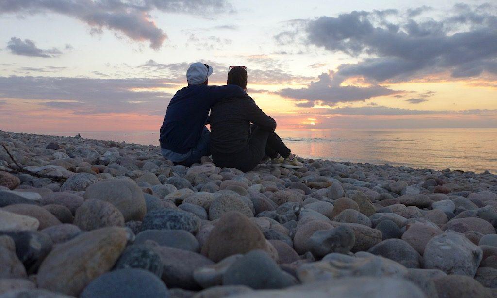 Ein Pärchen genießt den Sonnenuntergang in Udshold Strand