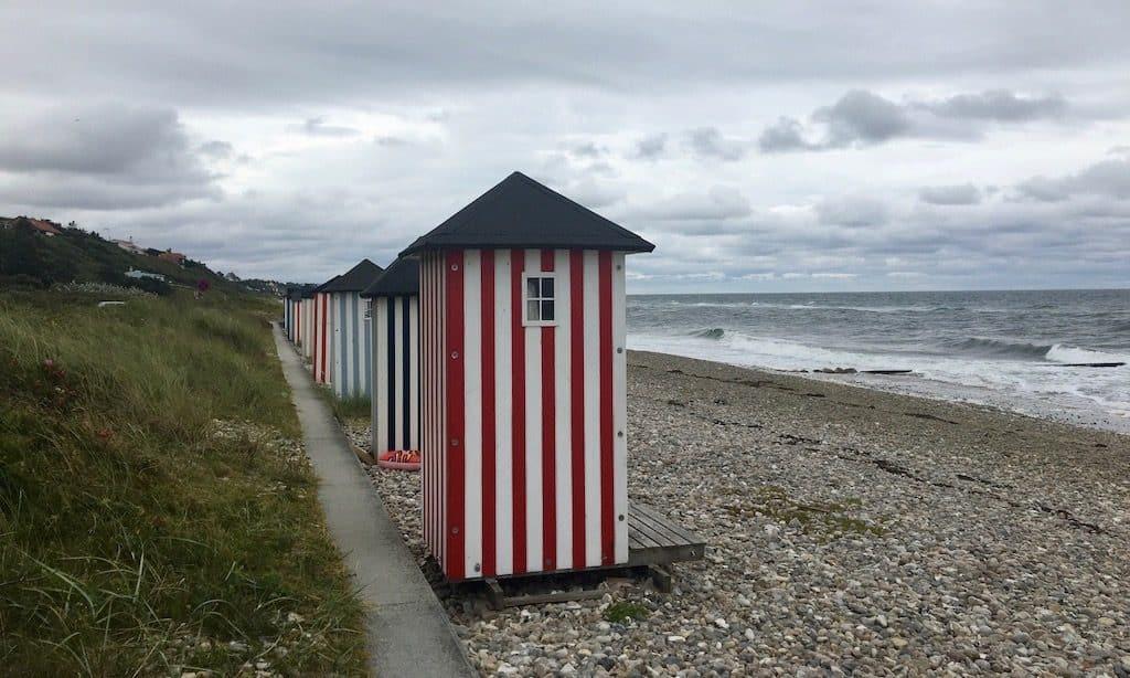 Buntgestreifte Badehäuser am Strand von Rågaleje bei bewölktem Wetter