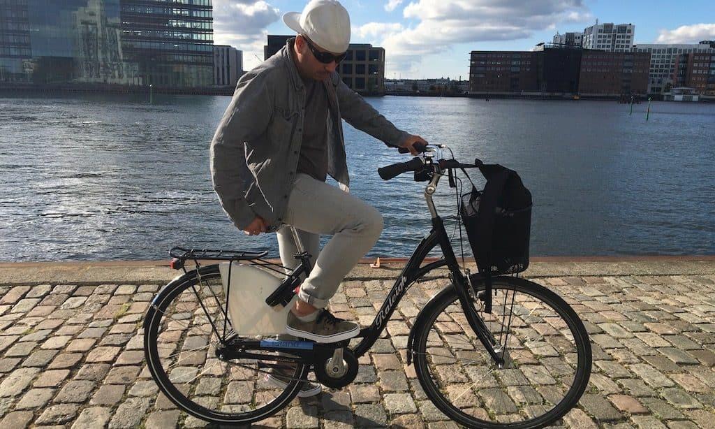 Ein cooler Mann auf einem Fahrrad in Kopenhagen am Wasser