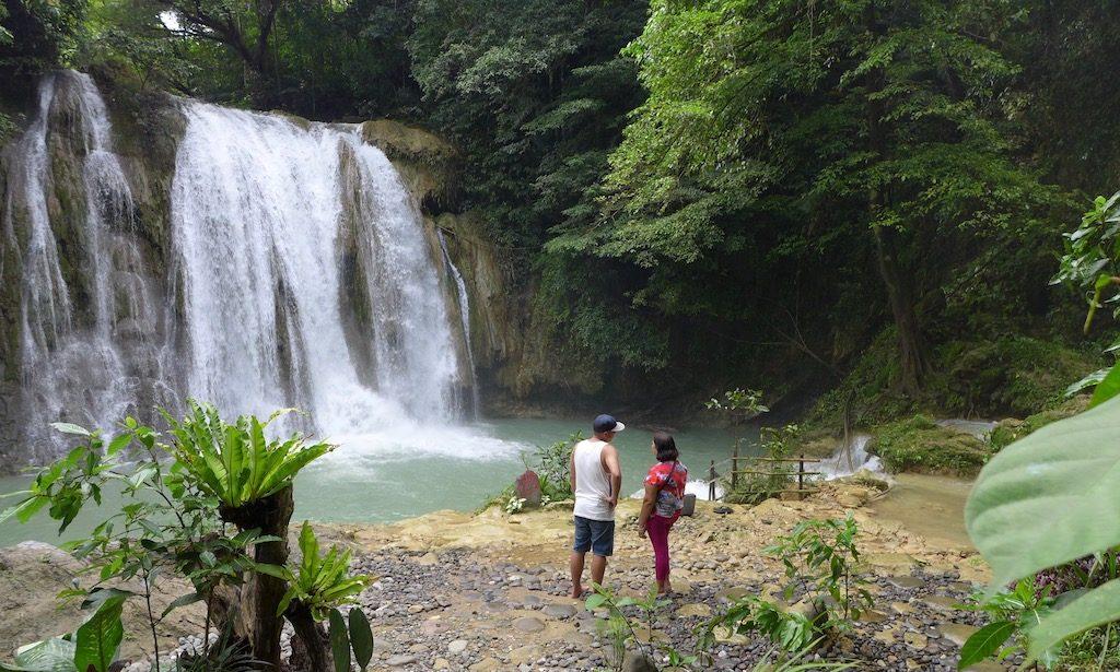 Urlaub auf den Philippinen - Zwei Menschen stehen vor dem Daranak Wasserfall