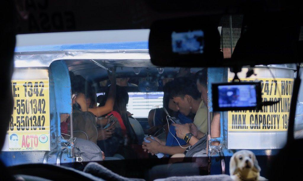 Asiaten im Jeepney. Alle gucken in ihr Handy