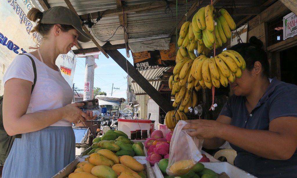 Ein Frau kauft Mangos am Gemüsestand in den Philippinen
