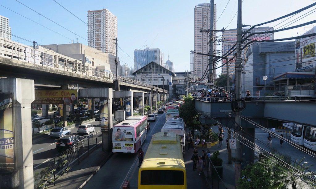 Starker Verkehr in Manila EDSA mit Wolkenkratzern im Hintergrund