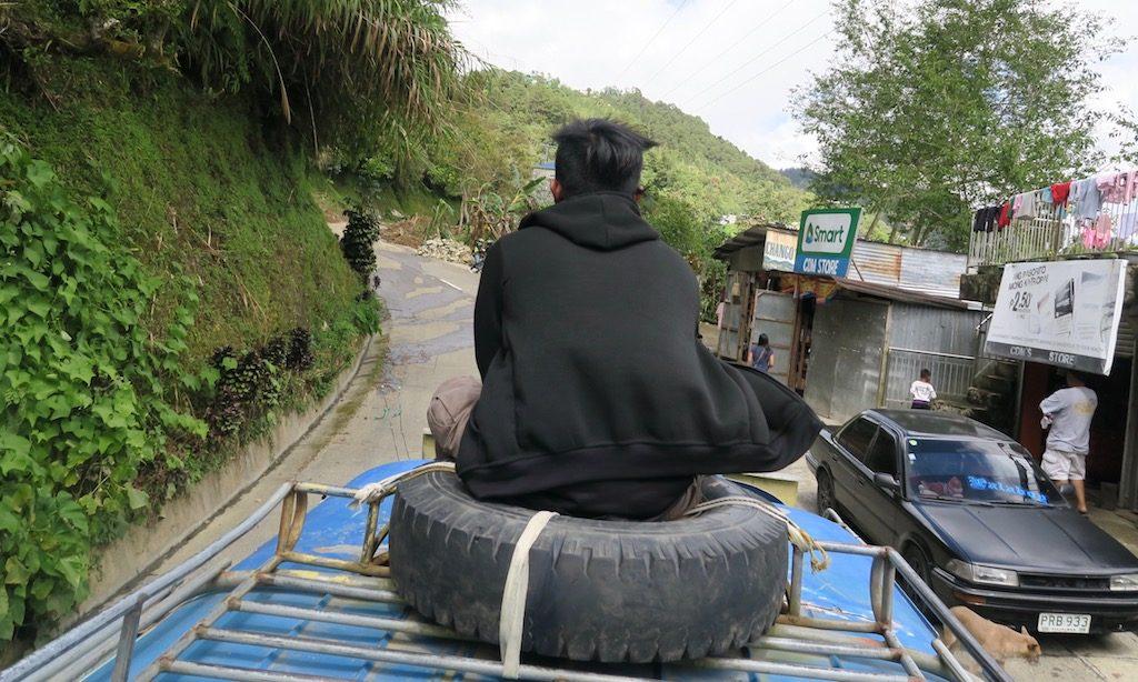 Ein Philippinen sitzt auf dem Dach eines Jeepneys