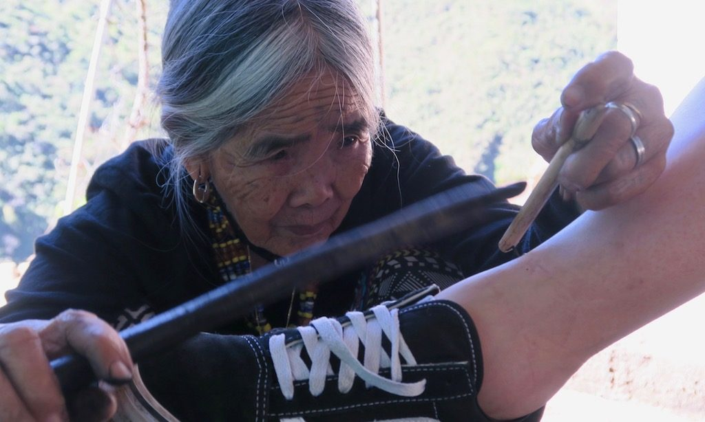 Nahaufnahme von Apo Whang-Od beim Tätowieren eines Fußknöchels