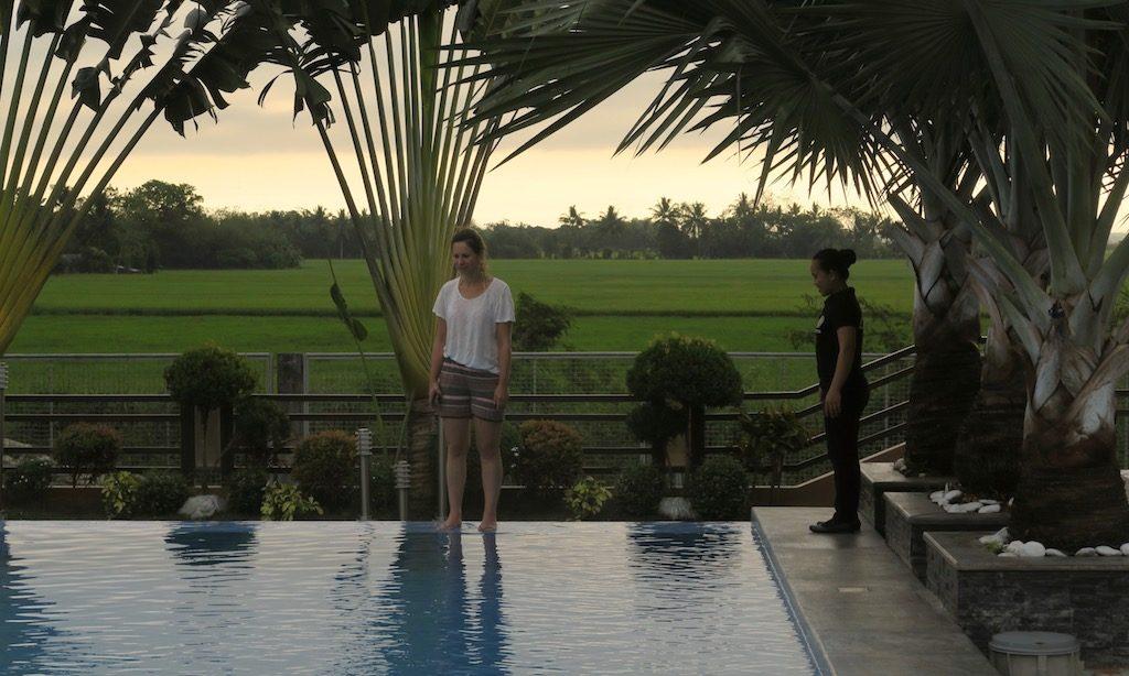 2 Frauen stehen am Pool des JAPI Hotels in Cauayan. Im Hintergrund ein Reisfeld