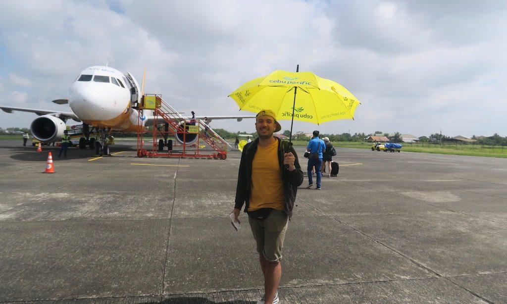 Ein Mann mit Sonnenschirm von Cebu Pacific Airlines vor einem Flugzeug