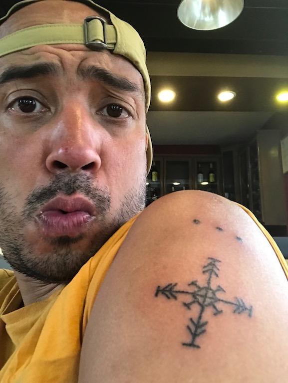 Ein Mann zeigt sein Oberarm-Tattoo von Apo Whang Od - ein Kompass und ihre Signature