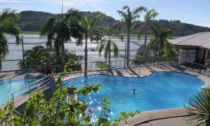 Der Pool mit Palmen und Blick auf Laguna de Bay beim Kuhala Bay Resort in Cardona am Laguna de Bay