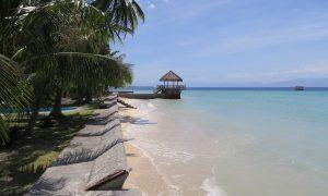 Türkises Meer, kleiner Strand und Palmen beim Les Maisons D'Itac in Ronda, Cebu, Philippinen