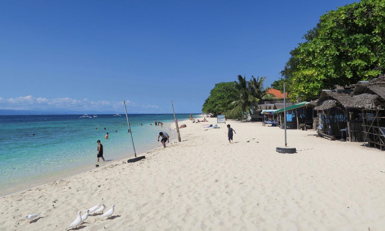Der White Beach von Moalbola. Weisser Sand, blauer Himmel und ein paar Badegäste.