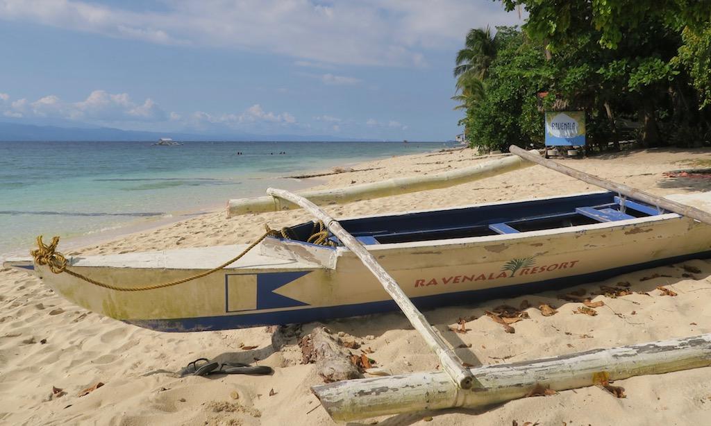 Ein Bangka von Ravanela Beach Resort liegt einsam und verlassen am White Beach in Moalboal
