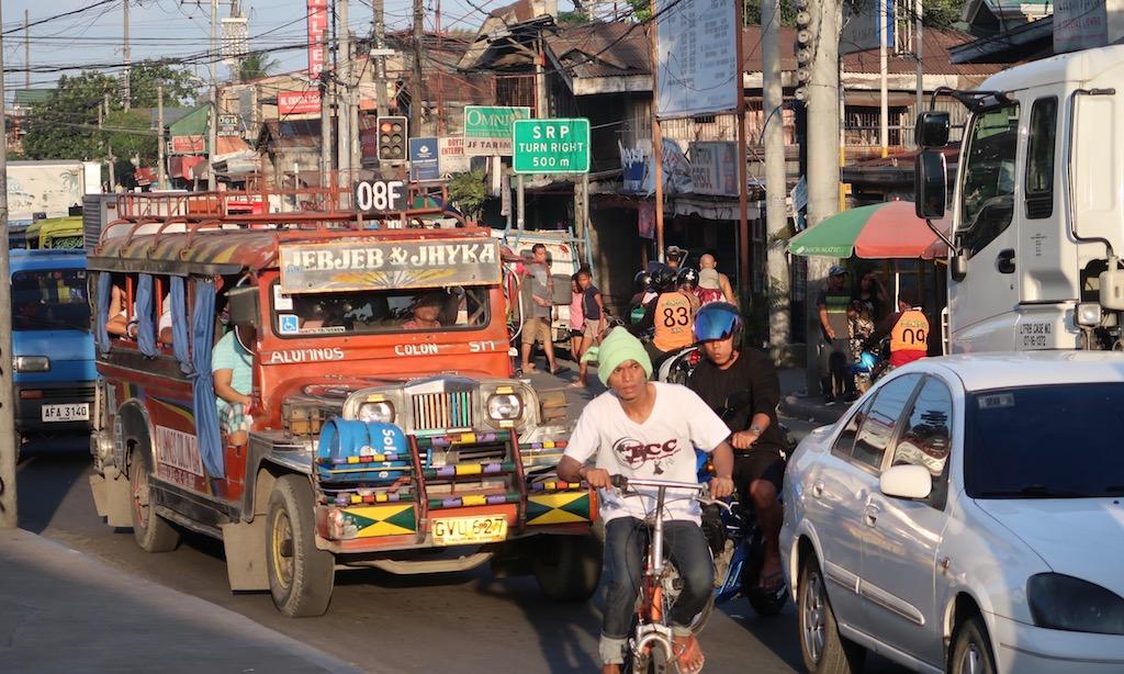 Ein Fahrradfahrer mit Wollmütze vor einem roten Jeepney in den vollen Straßen von CEBU City