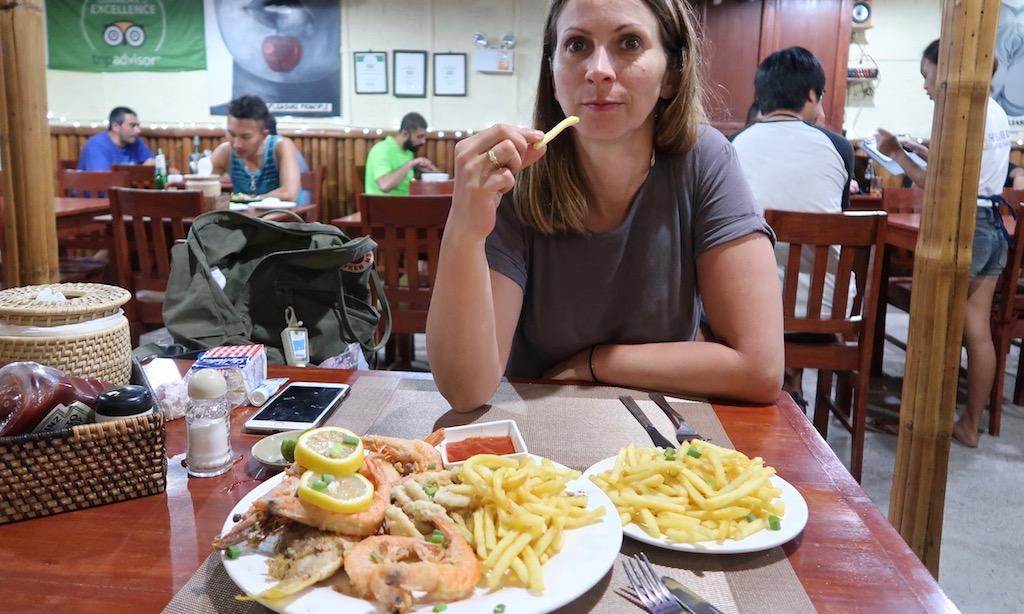 Ein hübsche Frau ist Pommes von einer Seafoodplatte in der Pleasure Principle Resto Bar am Panagsama Beach