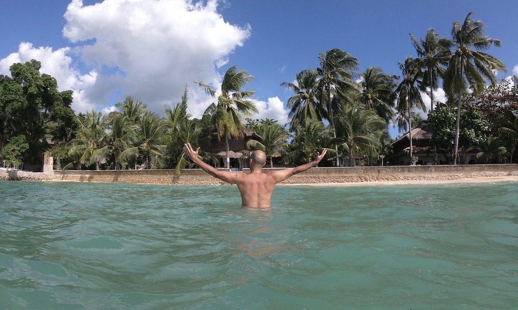 Ein muskulöser Mann im Meer streckt seine Arme aus. Im Hintergrund seht ihr die Palmen und das Les Maisons D'Itac, Happy Place in Ronda bei Moalboal