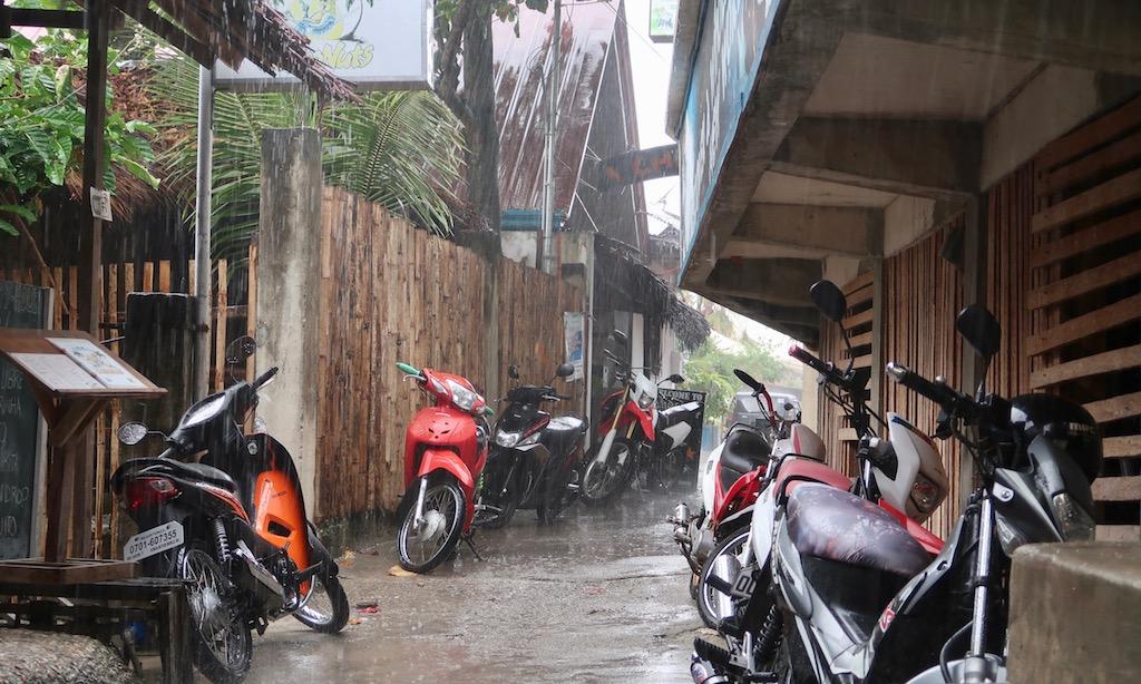 Parkende Scooter in einem Durchgang am Panagsama Beach bei starkem Regen