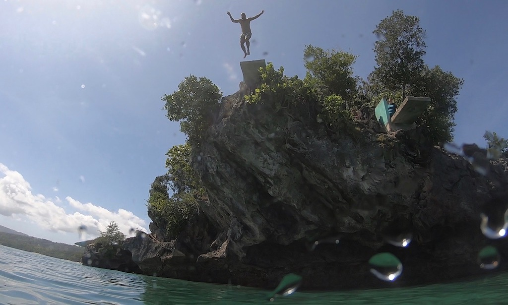 Bendja springt von der Sprungplattform am Salagoong Beach. Es ist aus dem Wasser heraus gefilmt
