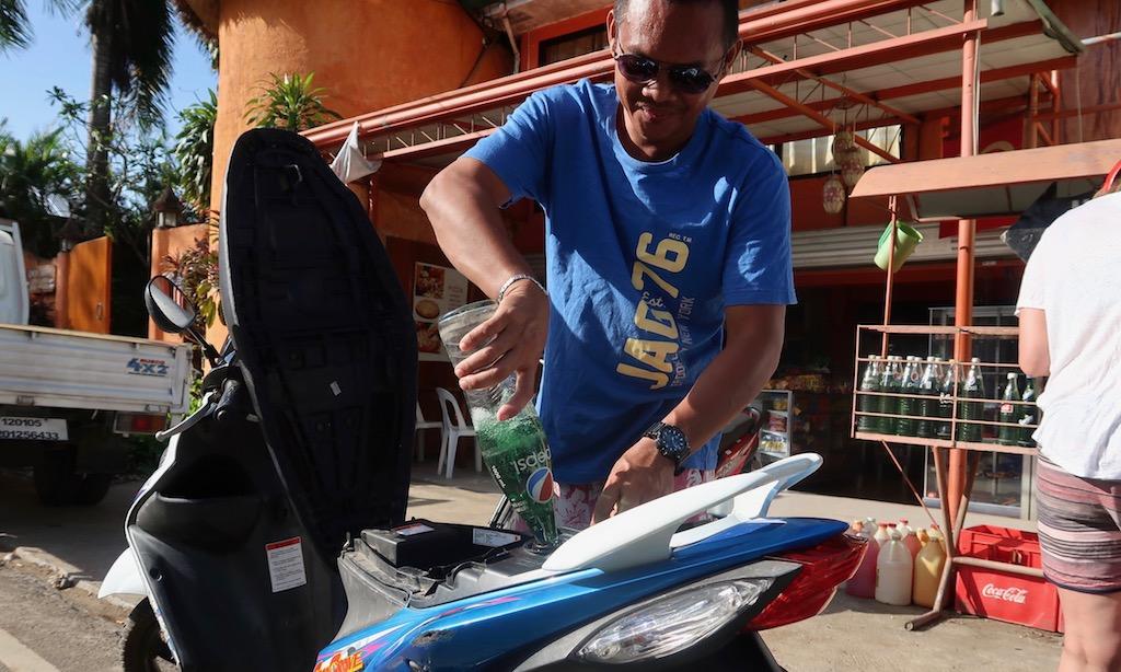 Tanken auf philippinische. Eine Pepsiflasche mit Benzin wird in den Scooter getankt