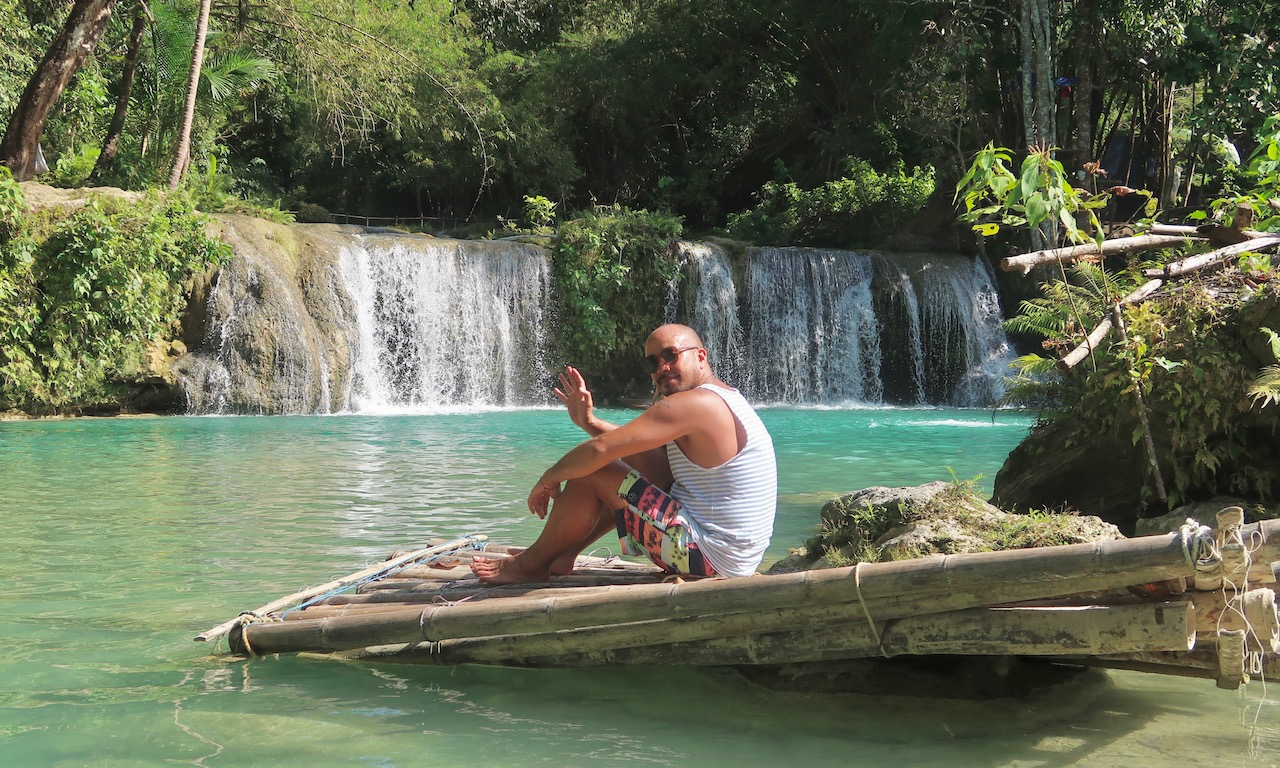 Bendja sitzt auf einem Floss bei den Cambugahay Falls und winkt in die Camera
