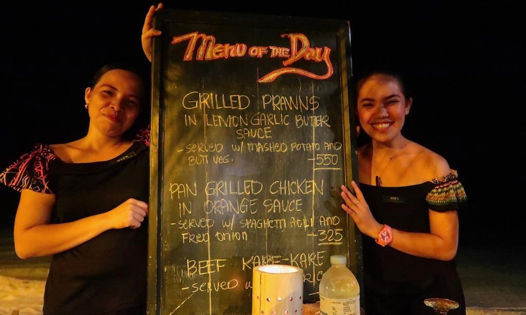 2 weibliche Angestellte präsentieren die Menütafel des Salamanders Restaurant Coco Grove