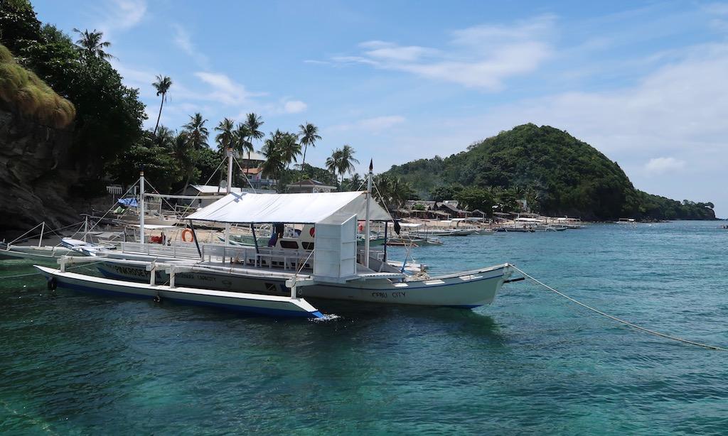 Bangkas liegen vor dem Hauptstrand von Apo Island wo Turtlemania stattfindet
