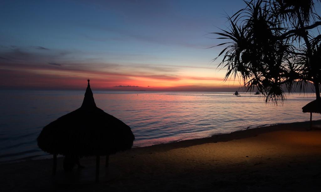 Bilderbuch Sonnengang beim Turbod Beach. Die Himmel färbt sich von dunkelblau ins rot.