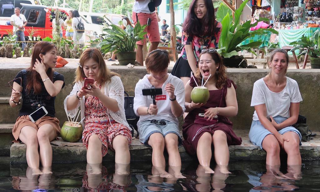 1 Chinesische Reisegruppe und eine deutsche Touristen sitzen lachend am Becken des Balate Trees